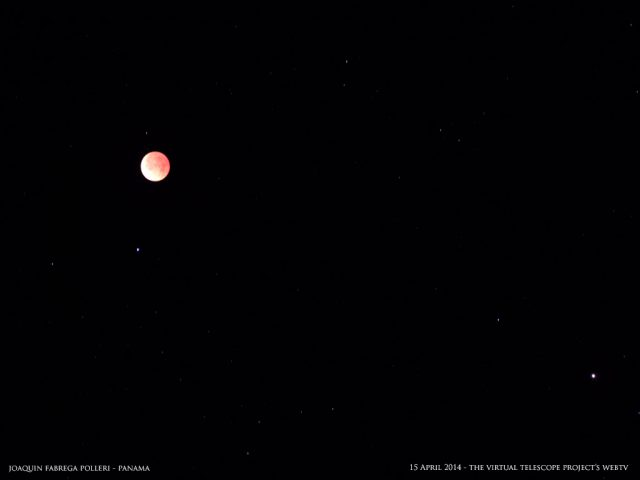 "The Red Moon, totally eclipsed, did not ""eclipsed"" other beauties. This image captures the bright, bluish light of Spica and the rusty hue of planet Mars, on the right. Image by Joaquin Fabrega Polleri, shared live via The Virtual Telescope Project"