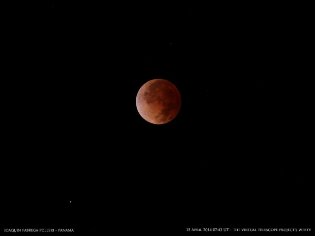 The Moon dresses its most elegant dress, a couple of minutes before the time of greatest eclipse, at totality. The bluish star Spica is on the bottom. Image by Joaquin Fabrega Polleri, shared live via The Virtual Telescope Project