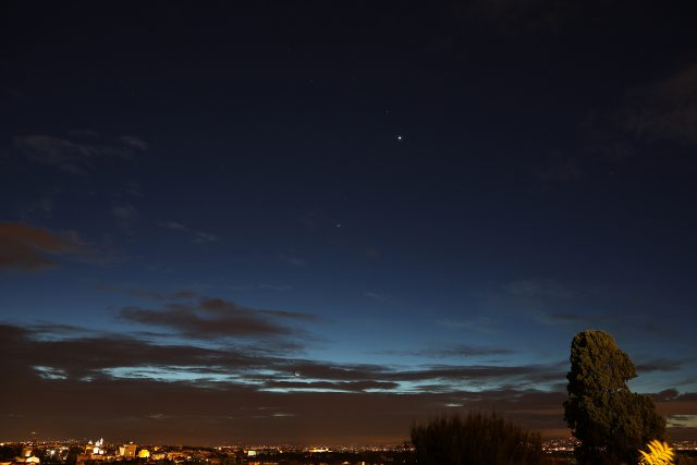 In a beautiful blue sky, Venus, Regulus, Mars, Jupiter, the Moon and Mercury are making a unique apparition above the Roman roofs, as seen from Gianicolo, in Rome