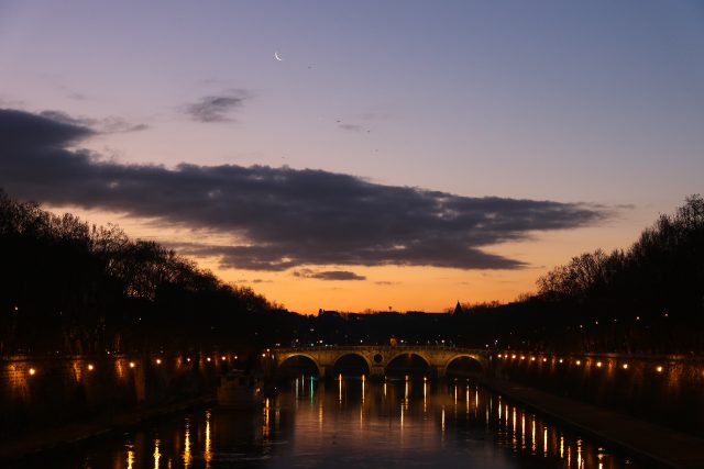 The Moon and Venus are shining at dawn above the colorful waters of the Tevere river, in Rome