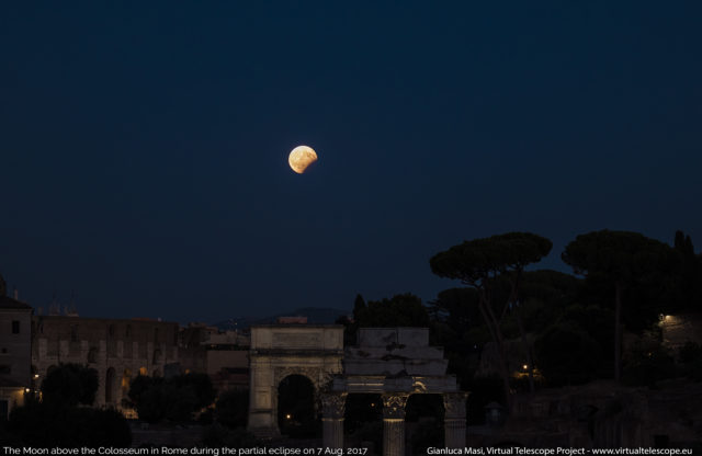 Later in the evening, the eclipsed Moon hangs above the Colosseum and the Titus' Arch. 07 Aug. 2017, 18:42 UT