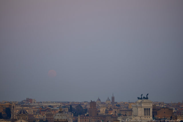A pale, very elegant Supermoon rises above Rome: the thick haze makes it quite red. 19 Feb. 2019