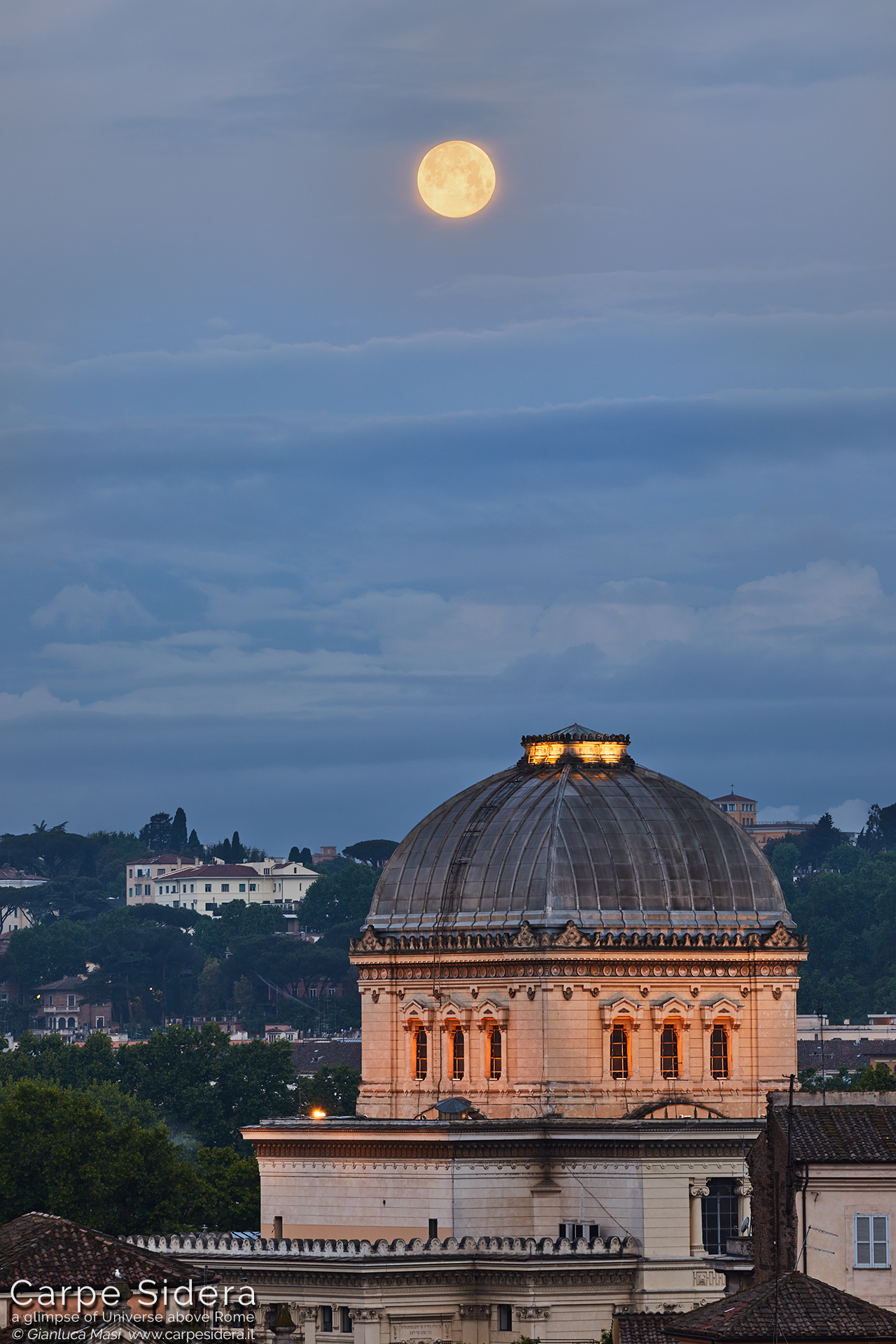 """The May 2019 """"Blue Moon"""" is ready to set and hangs above the Great Synagogue of Rome"""