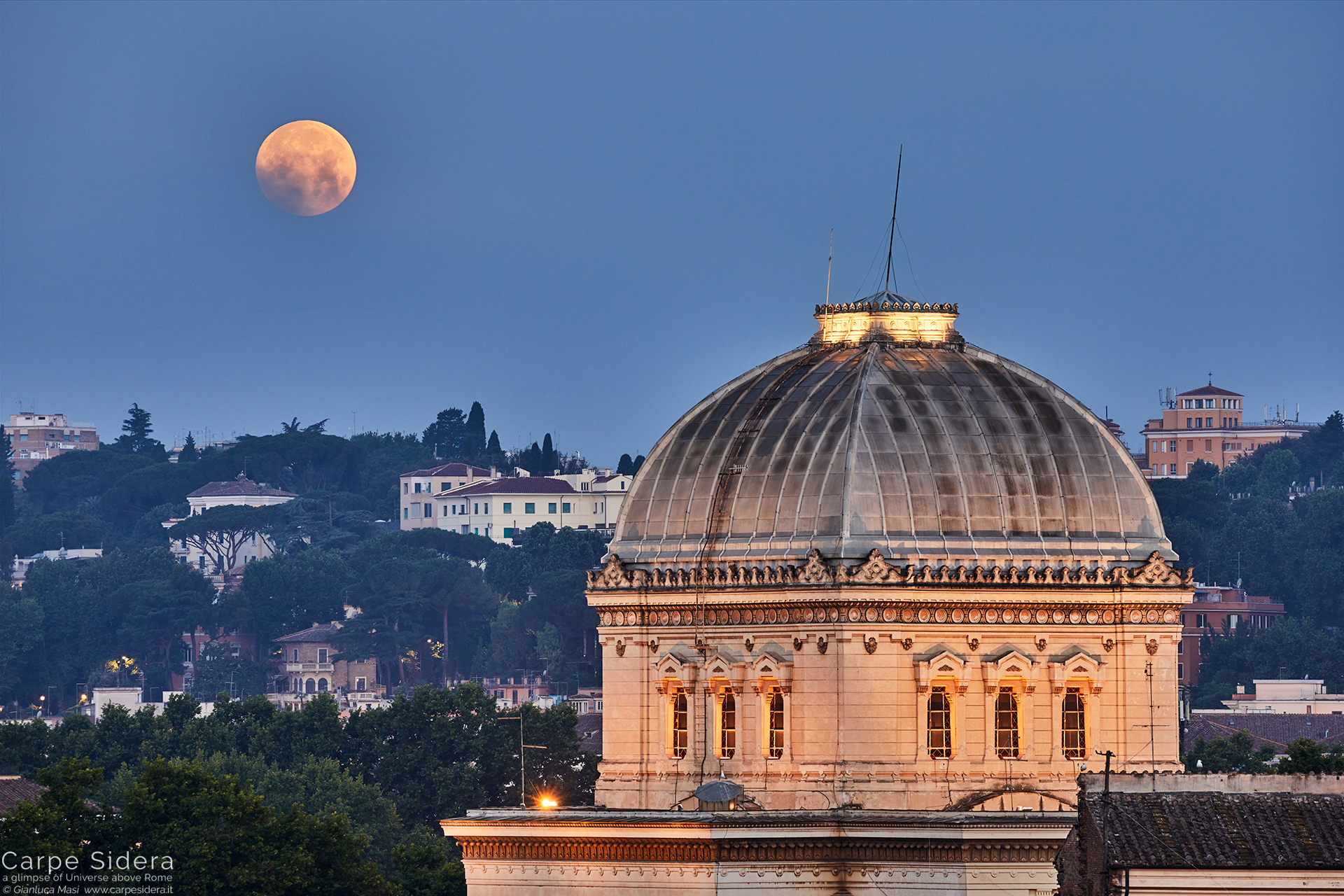 While it sets behind the Synagogue of Rome, the full Moon plays with some clouds